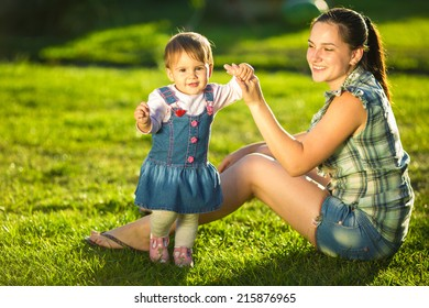 Baby girl is doing her first steps with mothers help. Cute little girl learns to walk with her young mom helping her in the sunny garden outdoors. Happy family  childhood and motherhood concept.