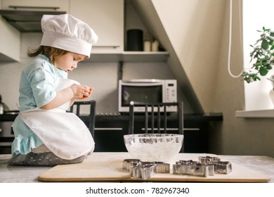 Baby girl dressed in a chefs preparing dough in the kitchen sitting on the table