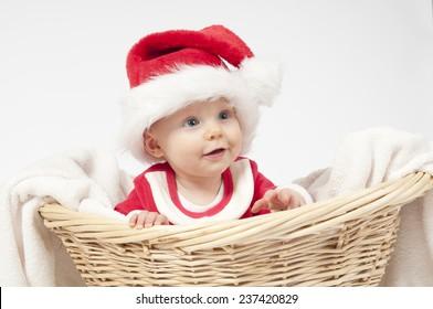 Baby girl dressed as santa on white background