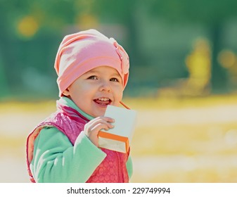 baby girl drinking juice in the autumn outdoors