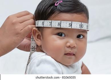 Baby girl during pediatric exam, head circumference