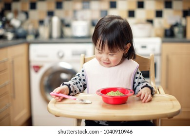 Baby girl eat mashed avocado at home kitchen
