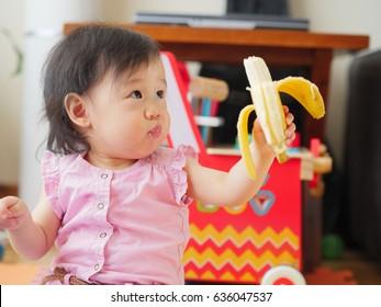 baby girl eating banana at home