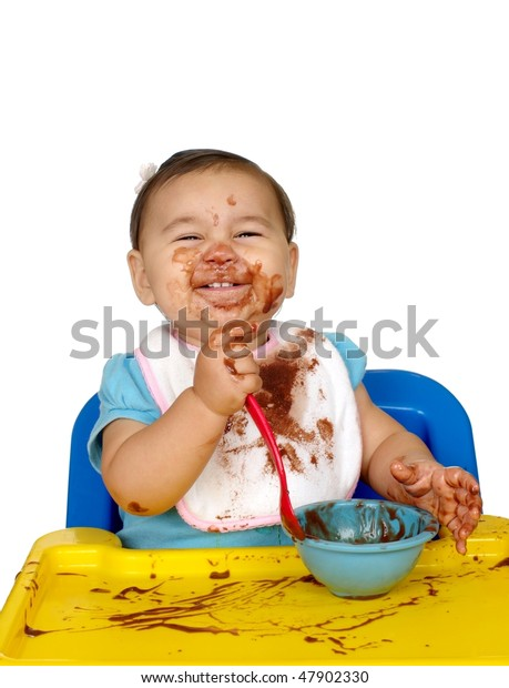 baby girl eating chocolate pudding, messy face, one year old
