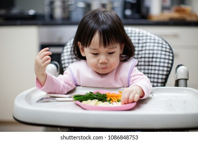 Baby girl eating healthy vegetable at home