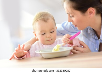 Baby girl eating lunch with help of her mommy
