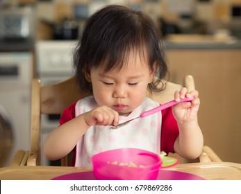 baby girl eating mashed potatoes at home