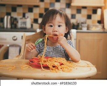 baby girl eating messy spaghetti