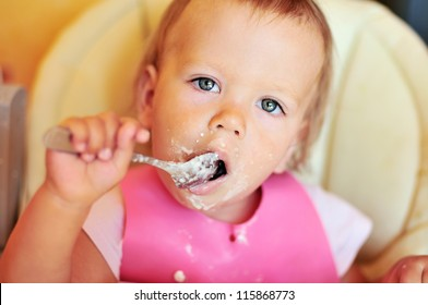 baby girl eating on her own with big spoon