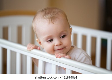 A baby girl of eight months is looking out of its bed. Closeup