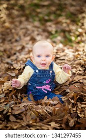Baby girl in fall leaves