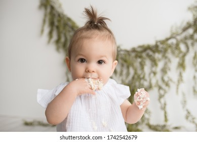 Baby girl first birthday cake smash on a white wood set in a white background and white cake