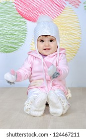Baby girl with a funny wool hat and mittens