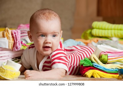Baby girl with heap of baby's wear laying on checked blanket