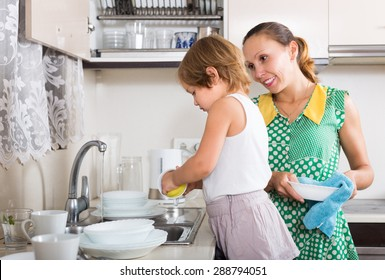 Baby girl helping mother washing dishes in the kitchen. Focus on girl
