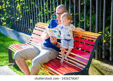 baby girl and her father reading a primer, sitting on a bench