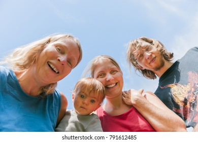 Baby girl with her grandmother, her mother and her uncle against sky