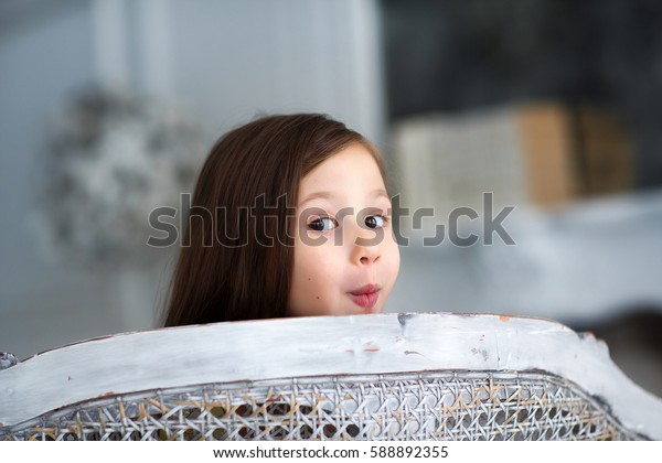 Baby girl hiding behind a chair, black-haired toddler