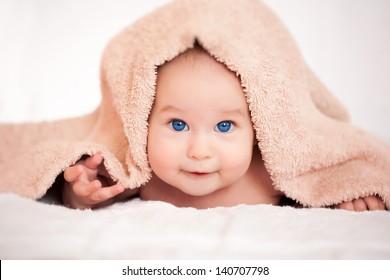 baby girl is hiding under the beige blanket