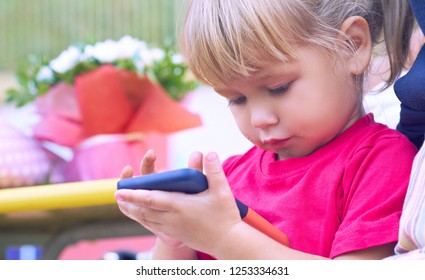Baby girl holding a mobile phone. Little Caucasian girl playing with smartphone in summer park. Child learning how to use modern electronic devices