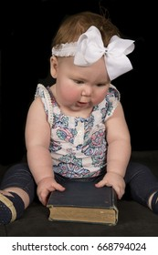 A baby girl is holding onto a book looking down, she cant wait to get it opened up.