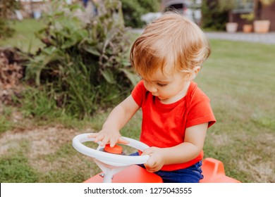 Baby girl honking horn of toy car - Kempen, Germany