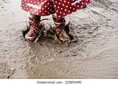 Baby girl jumping up and down on muddy puddles. She is wearing dotted raincoat and boots
