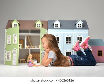 Baby Girl Kid playing with doll house stuffed with mini furniture toys and doll lying on a floor in play room at home or kindergarten