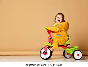 Baby girl kid riding her first bicycle tricycle in warm yellow overalls looking up on screaming grey background