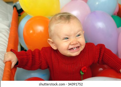 Baby girl laughing rounded with colorful balloons