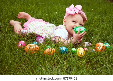 Baby girl laying in the grass with an assortment of colored Easter eggs