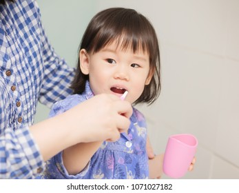 baby girl learn how to brush teeth