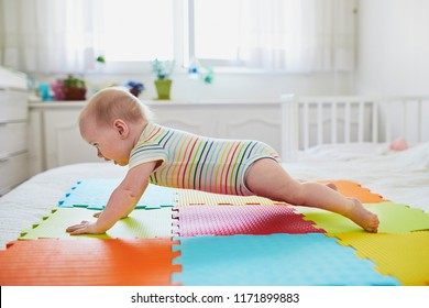 Baby girl learning to crawl. Little child lifting her body on arms. Infant kid in sunny nursery