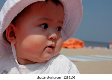 baby girl looking at the beach