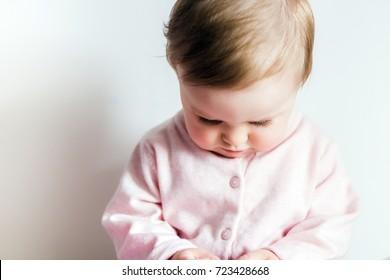 Baby girl looking down sad