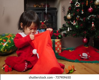 Baby girl looking for her Christmas gift