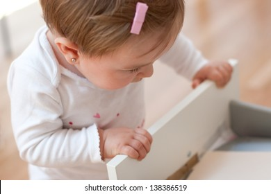 Baby girl looking inside a drawer with curiosity. Risks at home with little children. Focus in the eye.