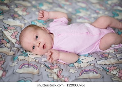 Baby girl looking into the camera in her bed. Newborn child active at home