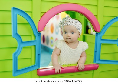 baby girl  looking out from plastic play house