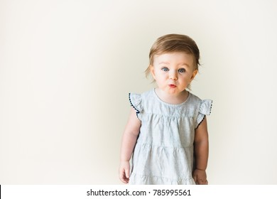 Baby girl looking surprised and aggressive, isolated on white