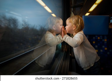 Baby girl looking through window. She travels on a train.