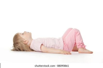 The baby girl is lying on the floor bend one's knees on white background