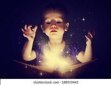 baby girl with magic book on a dark background