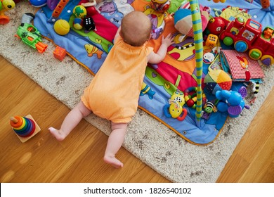 Baby girl with many colorful toys. Little child lying on playmat. Infant kid in nursery.