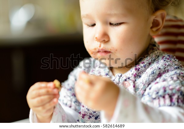 Baby girl with messy face during eating in kitchen. Nice one-year-old child eats and looks at his hands. Feeding cute baby at home. Portrait of beautiful toddler with food on blurred background indoor