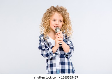 baby girl with microphone smiling singing,Fat girl singing song into microphone. Young star, looking for talents.