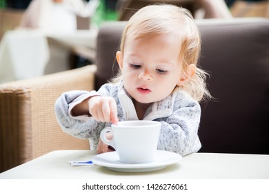 baby girl mixing sugar in a cup of tea