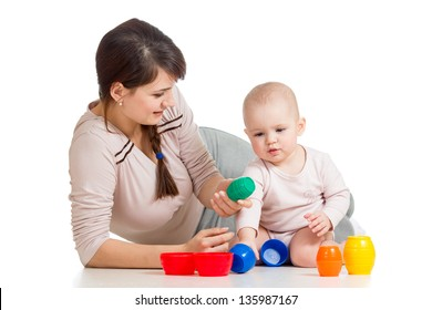 baby girl and mother playing together with colorful toys