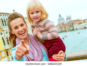 Baby girl and mother poiting in camera while standing on bridge with grand canal view in venice, italy