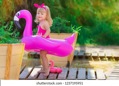 Baby girl on beach with pink flamingo dressed in stylish swimming wear posing on wooden floor. Scene on vacation on sea side of a cute lady smiling and enjoy life time childhood infancy